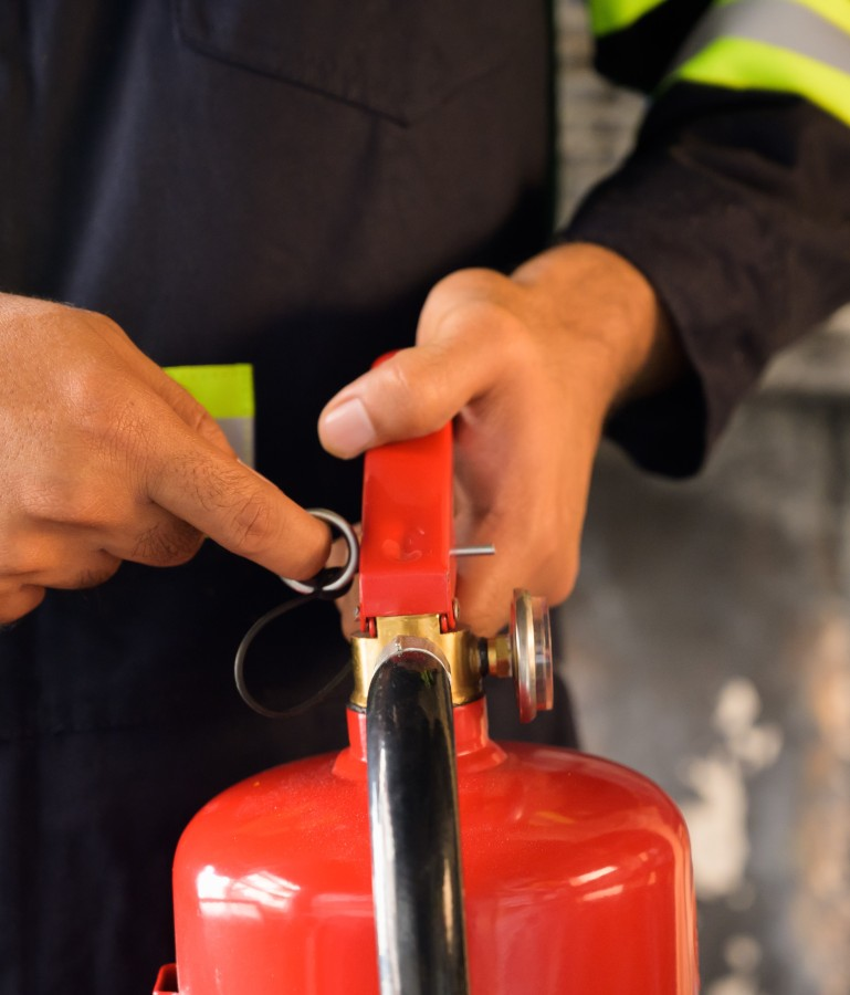 vecteezy_close-up-of-fireman-pulling-pin-of-fire-extinguisher_1227579--1-